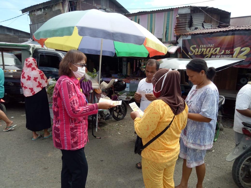 Staf Puskesmas Lolak membagikan leaflet kepada warga
