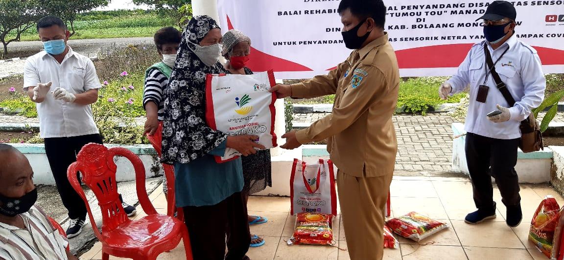 Kepala Dinas Sosial, menyerahkan secara simbolis bantuan paket sembako